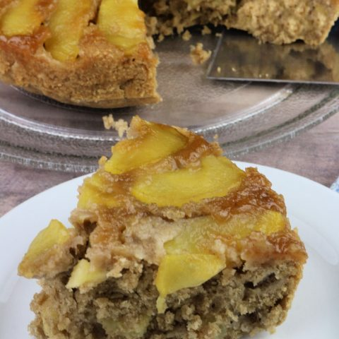 Slice of air fryer apple cake on white plate with rest of cake in background