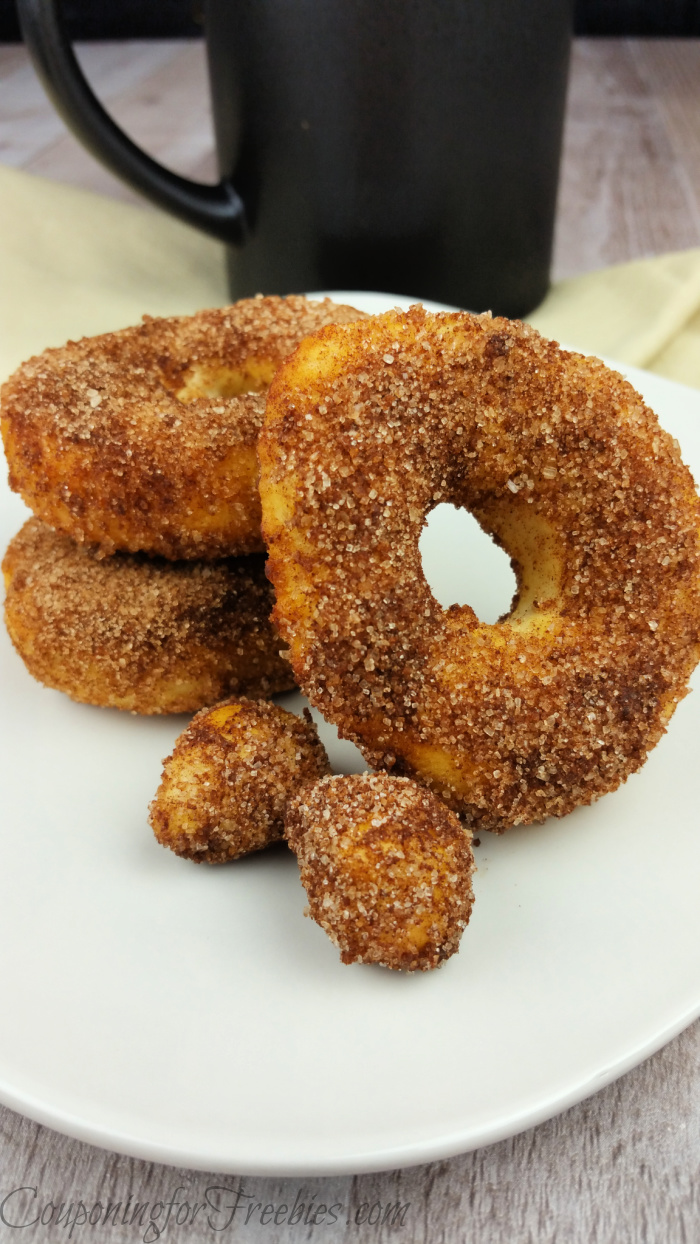 Cinnamon sugar air fryer donuts on while plate with black coffee mug in background