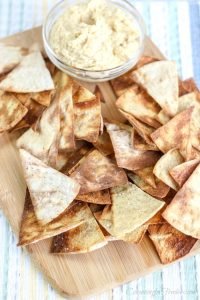 Cutting board with fresh baked pita chips and a glass bowl of hummus.