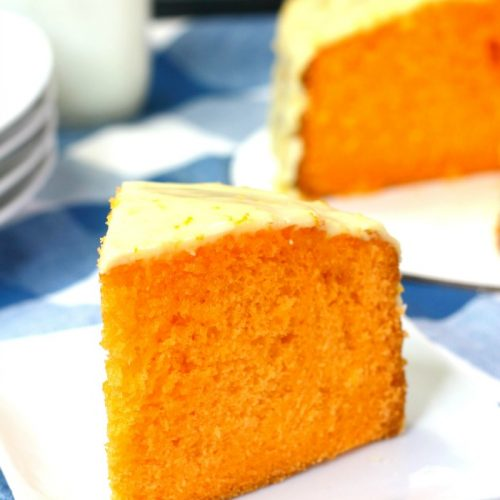 Slice of Instant Pot orange cake on white plate with rest of cake in background