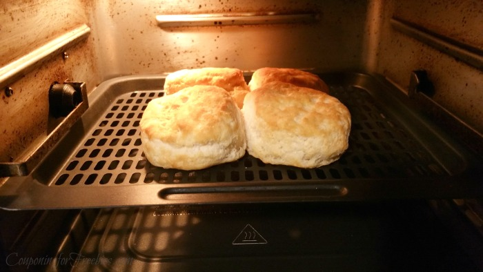 Four fresh baked biscuits on air fryer tray inside air fryer