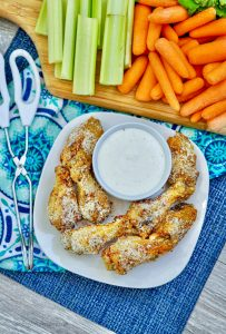 Garlic Parmesan Air Fryer Wings on white plate with fresh cut veggies in background