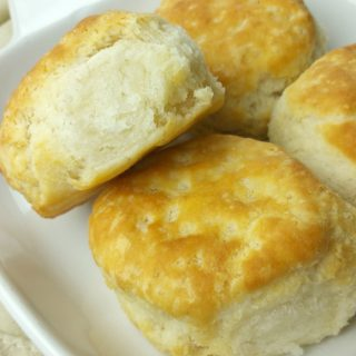Four fresh baked golden biscuits on white plate setting on tan cloth napkin