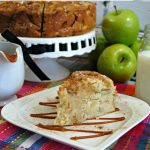 Slice of Irish Apple Cake on white plate with whole cake in background with green apples.