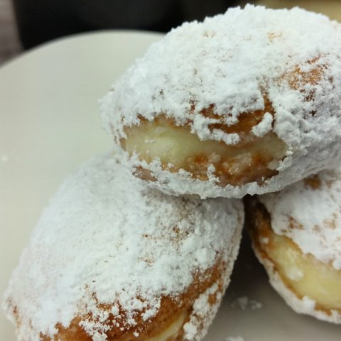 3 Pudding filled donuts coated in powdered sugar on white plate with black coffee mug in background
