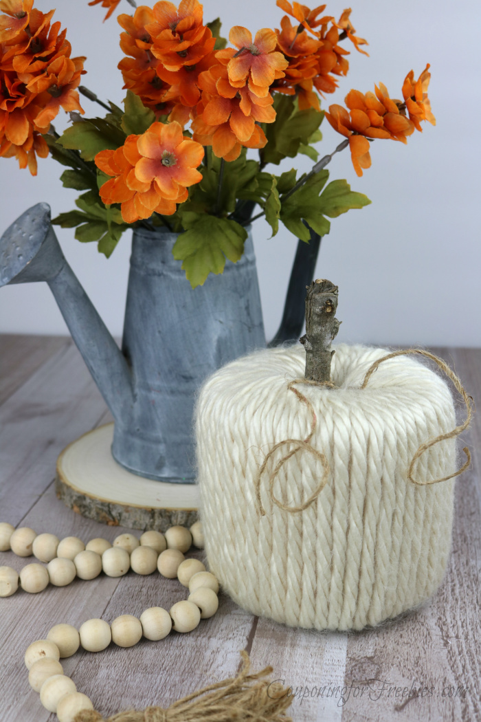 Finished yarn pumpkin with orange flowers in watering can in background and woods beads to the side