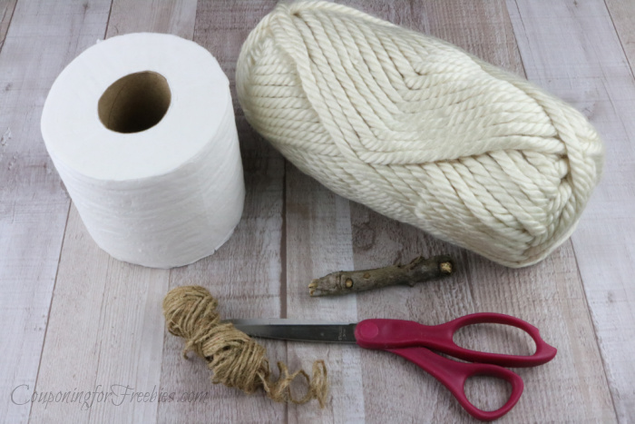 Yarn, toilet paper, scissors, stick and twine on wood background
